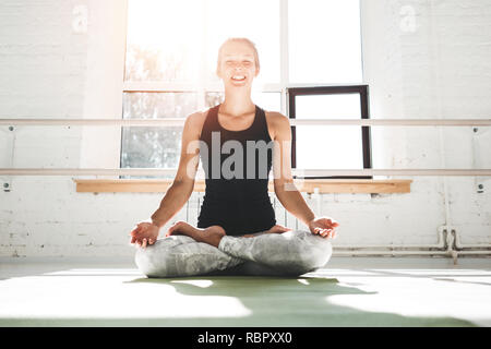 Happines fit woman practicing yoga poses in gym in the mowrning. Female in yoga pose on fitness mat. Yoga girl performs asana - Stock Photo