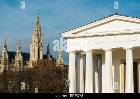 The Doric Theseus-Tempel temple, a replica of the Theseion in Athens, in the centre of the Volksgarten with the Town hall to the rear, Vienna, Austria - Stock Photo