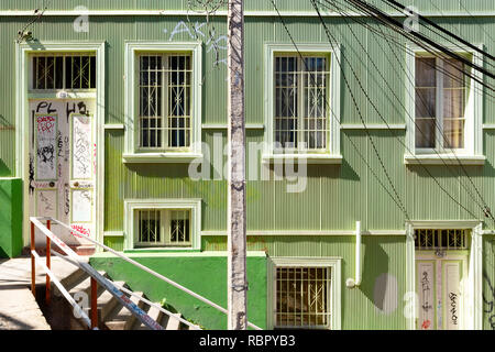 House front, painted green. in the backstreets of Valparaiso, Chile. - Stock Photo