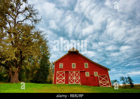An old red barn sits on a hillside of a wildlife refuge in rural Oregon under early morning cloudy skies. - Stock Photo