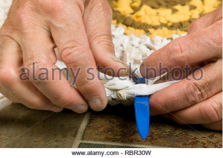 Close-up of a man doing toothbrush weaving creating a rug. (MR) - Stock Photo
