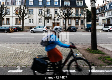 STRASBOURG, FRANCE- JAN 31, 2018: Strasbourg street at dusk with silhouette of cyclist woman commuting fast  - Stock Photo