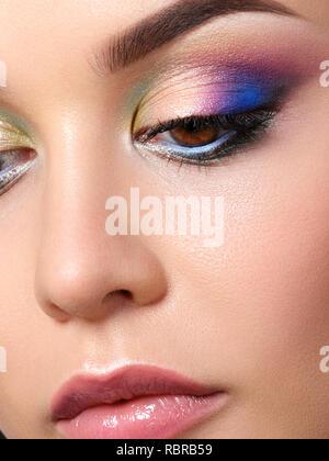 Portrait of beautiful woman with fashion makeup wearing blue earrings. Modern fashion makeup. Multicolor smokey eyes. Studio shot. Extreme closeup, pa - Stock Photo