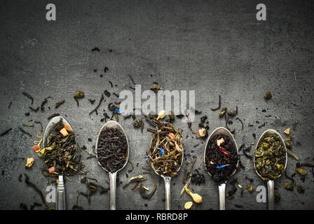 Various kinds of tea in spoons on black slate background. Dry Tea assortment. - Stock Photo