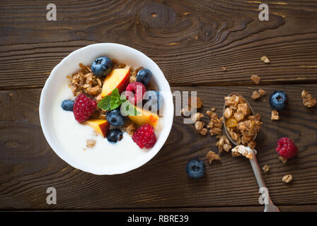 Yogurt with Granola  and fresh berries on  wooden table. Healthy breakfast. - Stock Photo