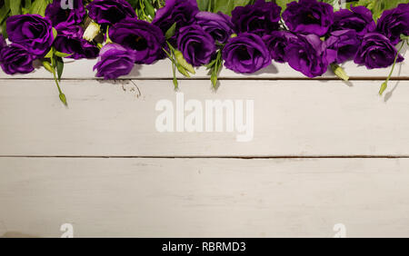 Violet flowers - eustoma, on a white wooden background. Copy space. - Stock Photo