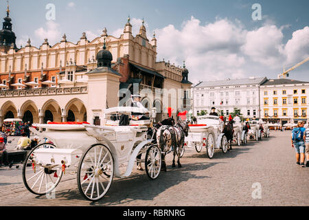 Krakow, Poland - August 28, 2018: Horses In Old-fashioned Coach Carriage Near Cloth Hall Building At Main Market Square In Sunny Summer Day. - Stock Photo
