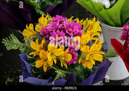Bouquet yellow lilies and purple chrysanthemums, wrapped in a decorative package with a print - Stock Photo