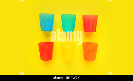 Plastic glass of various color isolated on yellow background - bright summer concept for design and banners - Stock Photo