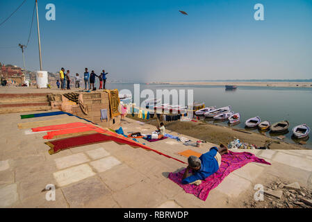 Life along the Ganges in Varanasi: man lies on a sheet in the wintery sunshine while boys fly kites in a distance. Varanasi, India - Stock Photo