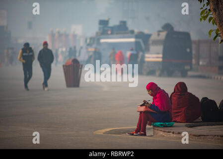 Early morning scene in front of the Red Fort in Delhi with woman sitting and writing on her notebook and pedestrians in the background. - Stock Photo