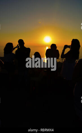 Silhouettes of people at viewpoint on the top of the hill, watching and photographing sunset over the sea - Stock Photo