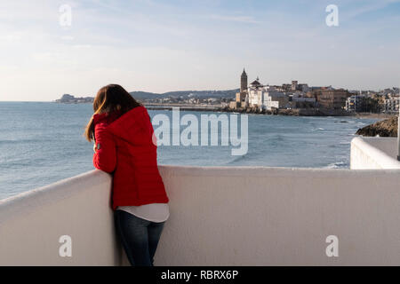 girl envisioning the horizon on the coast at the beach of sitges - Stock Photo
