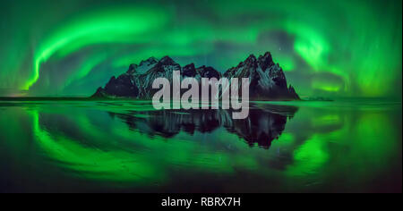 Reflections of aurora borealis around Vestrahorn mountains on Stokksnes black beach, Iceland - Stock Photo