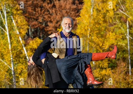 Happy, vital elderly couple dancing and having fun in a bright, sunny day on mountain meadow and birch forest in background - Stock Photo