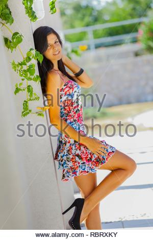 Looking at camera teen girl profile side-view three-quarter length body solo human being person young woman legs heels elegant elegance - Stock Photo