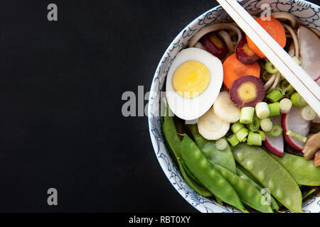 Udon noodle soup with fresh snow peas, carrots, spring onions and egg.  Flat lay with copy space. - Stock Photo