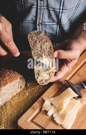 Preparing healthy vegetarian bruschettas on rustic wooden table. Top view on male hands spreading soft cheese on rye wholegrain bread. Making sandwiches for snack - Stock Photo
