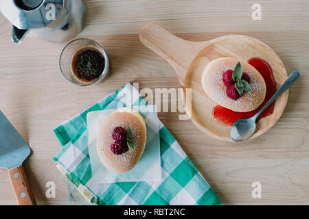 Wooden desk with Japanese cheesecake and cup of coffee in morning, Top view, Flat lay. - Stock Photo