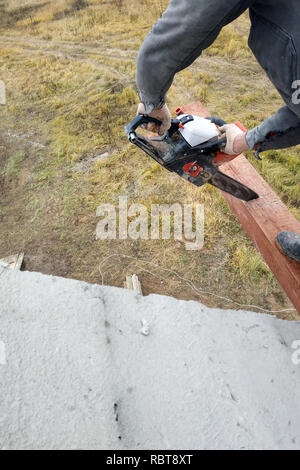 woodworker with a chainsaw makes drank on a wooden beam construction of houses 2018 - Stock Photo