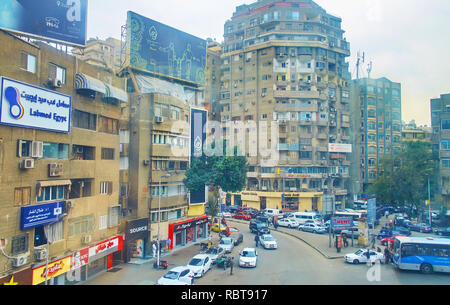 GIZA, EGYPT - DECEMBER 19, 2017: The busy Lebanon Square in Mit Akaba neighborhood with shabby high-rises, multiple billboards, chaotic traffic and nu - Stock Photo