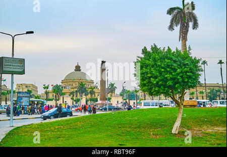 GIZA, EGYPT - DECEMBER 19, 2017: Enjoy the garden in Nahdet Masr square with a view on historic building of Faculty of Arts of Cairo University, on De - Stock Photo