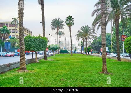 GIZA, EGYPT - DECEMBER 19, 2017: Walk along the scenic garden in Nahdet Masr square with a view on the dome of Faculty of Arts building of Cairo Unive - Stock Photo
