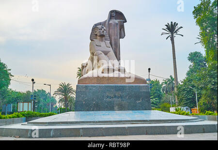 GIZA, EGYPT - DECEMBER 19, 2017: Impressive Nahdet Masr statue or Egypt's Awakening represents the peasant woman and Sphinx, surrounded by lush greene - Stock Photo