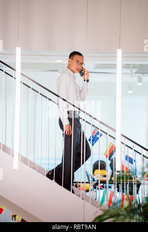 An Asian Chinese man in a shirt in professional shirt and pants walking down steps while he talks on his smartphone. - Stock Photo