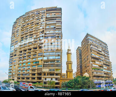 GIZA, EGYPT - DECEMBER 19, 2017: The living buildings at the Cairo University Bridge, with the small mosque, hidden between them, on December 19 in Gi - Stock Photo