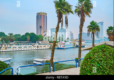 GIZA, EGYPT - DECEMBER 19, 2017: The green bank of Gezira Island is occupied by the tourist ships and floating restaurants, well seen from the bank of - Stock Photo