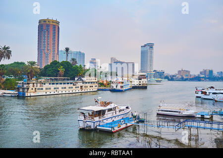 GIZA, EGYPT - DECEMBER 19, 2017: The tourist boats, floating restaurants and cruise ships are moored at the banks of Giza and Gezira Island on Nile ri - Stock Photo