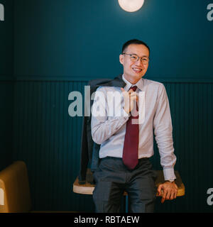 Portrait of an Asian businessman in a suit and tie leaning against a trendy blue booth in his office. He is smiling confidently. - Stock Photo