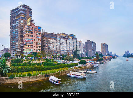 GIZA, EGYPT - DECEMBER 19, 2017: The residential high-rises of Al Doqi neighborhood and the line of ornamental gardens along the bank of Nile river, o - Stock Photo