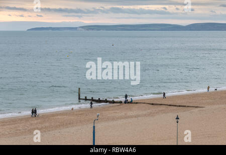 Bournemouth, Dorset, UK. 12th January 2019. Dog walkers wrap up warm to take their dogs out on the beach in Bournemouth on a winters day. Credit: Thomas Faull/Alamy Live News - Stock Photo