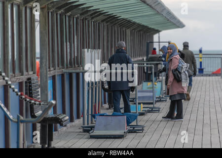 Bournemouth, Dorset, UK. 12th January 2019. Two women smile at a man walking on Boscombe Pier on a winters day. Credit: Thomas Faull/Alamy Live News - Stock Photo