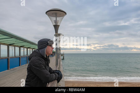 Bournemouth, Dorset, UK. 12th January 2019. Man in a warm hat looks out over Bournemouth from Boscombe Pier on a winters day. Credit: Thomas Faull/Alamy Live News - Stock Photo
