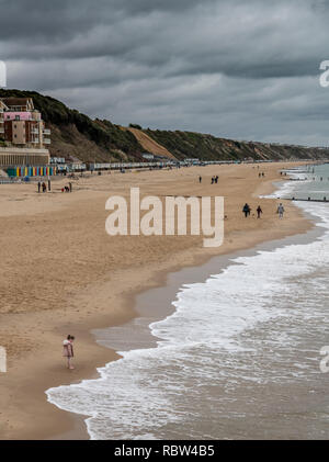 Bournemouth, Dorset, UK. 12th January 2019. Girl looks at the sea as other walk dogs in Bournemouth. Credit: Thomas Faull/Alamy Live News - Stock Photo