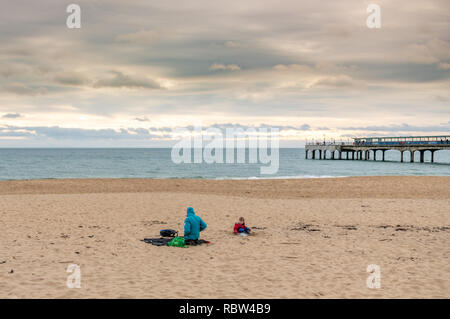 Bournemouth, Dorset, UK. 12th January 2019. Sitting on the beach, despite the cold weather in Bournemouth. Credit: Thomas Faull/Alamy Live News - Stock Photo