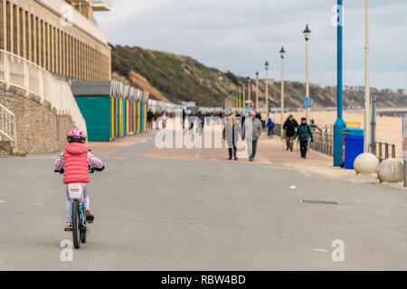 Bournemouth, Dorset, UK. 12th January 2019. Young girl rides a bike along the promenade in Boscombe, Bournemouth. Credit: Thomas Faull/Alamy Live News - Stock Photo