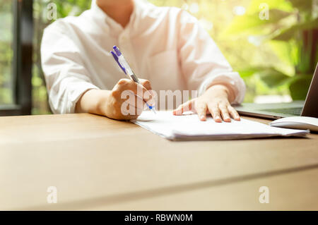 Hand filling document form contract with laptop an mouse on wooden table. - Stock Photo