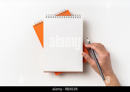 Design concept - Top view of 2 orange spiral notebook, white page and pencil, man hold pen isolated on background for mockup - Stock Photo