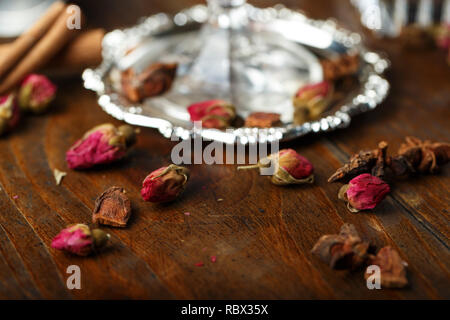 dried roses buds scattered on a wooden table. floral decorations - Stock Photo