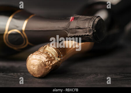 Two champagne bottles on black wooden table. Selective focus - Stock Photo