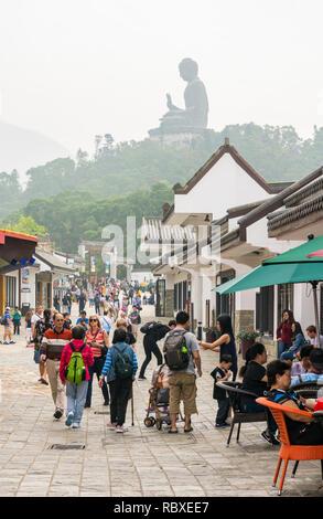 Ngong Ping village overlooked by haze covered Tian Tan Buddha, Lantau Island, Hong Kong - Stock Photo