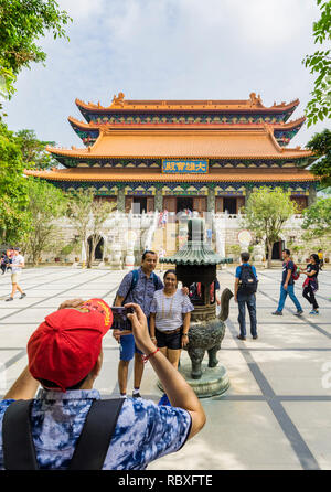 A tourist takes a photo of people at the Po Lin Monastery, Lantau Island, Hong Kong - Stock Photo