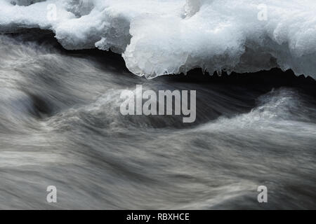 Detail view of fast flowing water of a small river, snow and ice on the shore, water movement in long exposure - Location: Germany, Saxony - Stock Photo