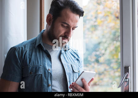 Sad man holding phone alone at home