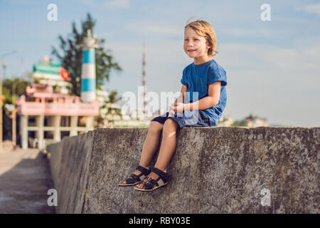 Boy traveler on the background Dinh Cau lighthouse symbol of the island Phu Quoc, Vietnam. Phu Quoc is a Vietnamese island off the coast of Cambodia i - Stock Photo