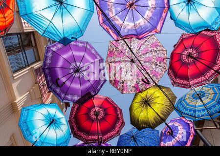 Colorful umbrellas in a city with blue sky - Stock Photo